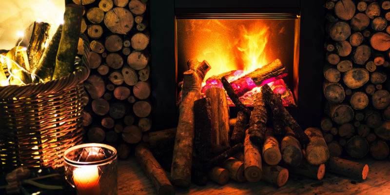 A fireplace in a home surrounded by logs