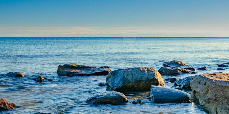 Rocks on a body of water under a blue sky