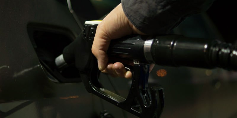 A person using a vehicle gas pump